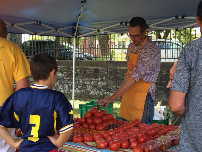 man standing behind a table with lots of red tomatoes talking to a young boy