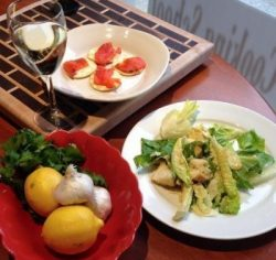 two plates of food with a glass of wine and bowl of lemons and garlic