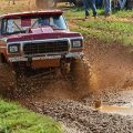 red truck driving through a mud pit