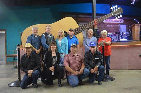 people in front of large guitar