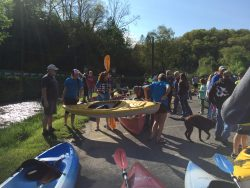 people holding canoes, kayaks and paddles getting ready for a race