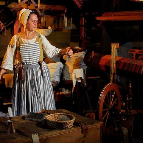 woman dressed in 18th century clothes spinning yarn
