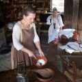 woman dressed in colonial period clothing making soap