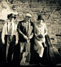 2 men and 1 woman dressed in 1920s clothes holding instruments