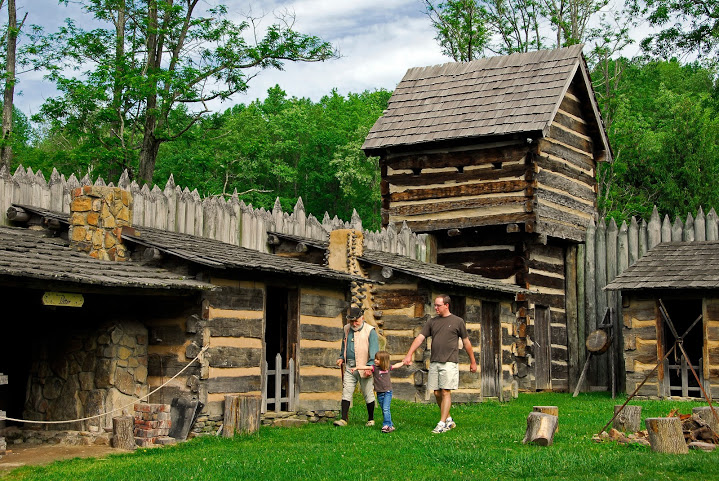 people walking by a wooden fort