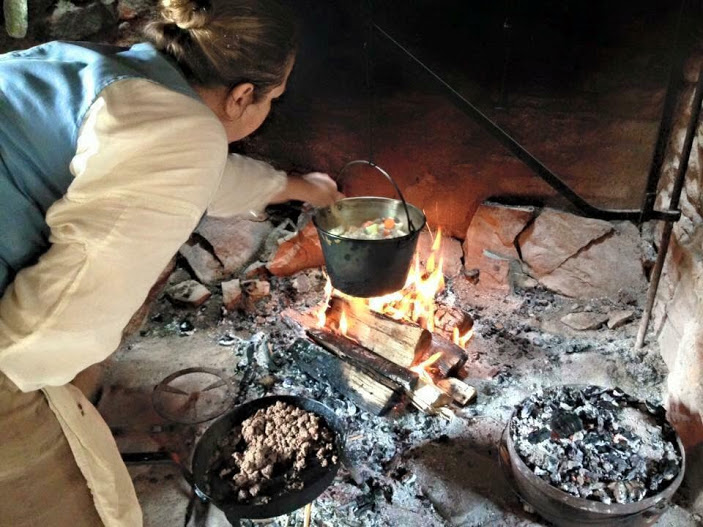 woman cooking over hearth