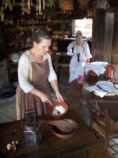 costumed interpreter demonstrating cooking