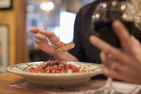 person holding a class of red wine and eating bruschetta from a bowl