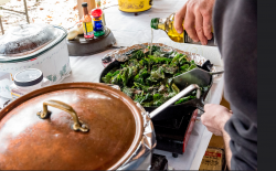 pweson adding oil to a pan of greens with a pot of chili beside