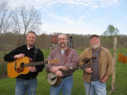 3 men standing outside holding guitars, and banjo