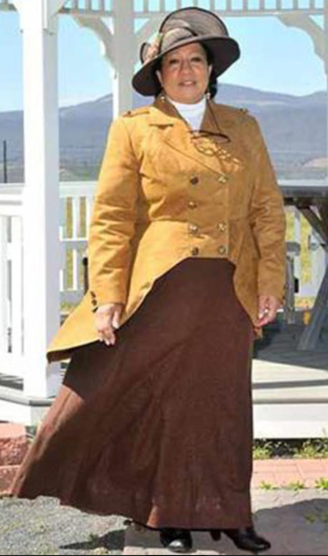 woman dressed in large hat with dark yellow jacket and long brown skirt