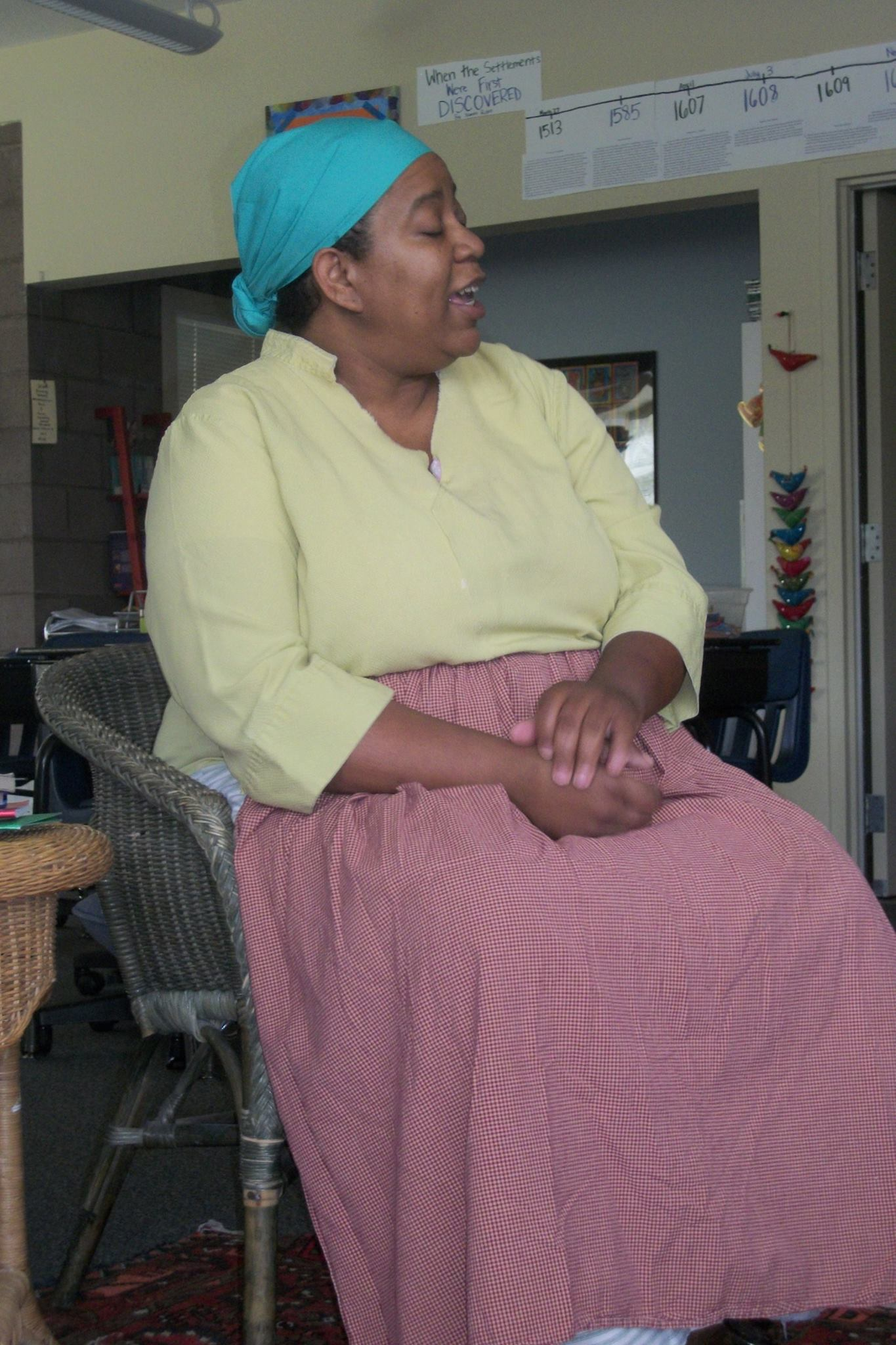African American woman sitting wearing clothing worn by a slave woman