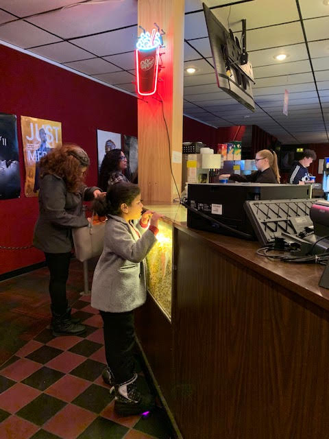 boy looking at the candy counter in a movie theater