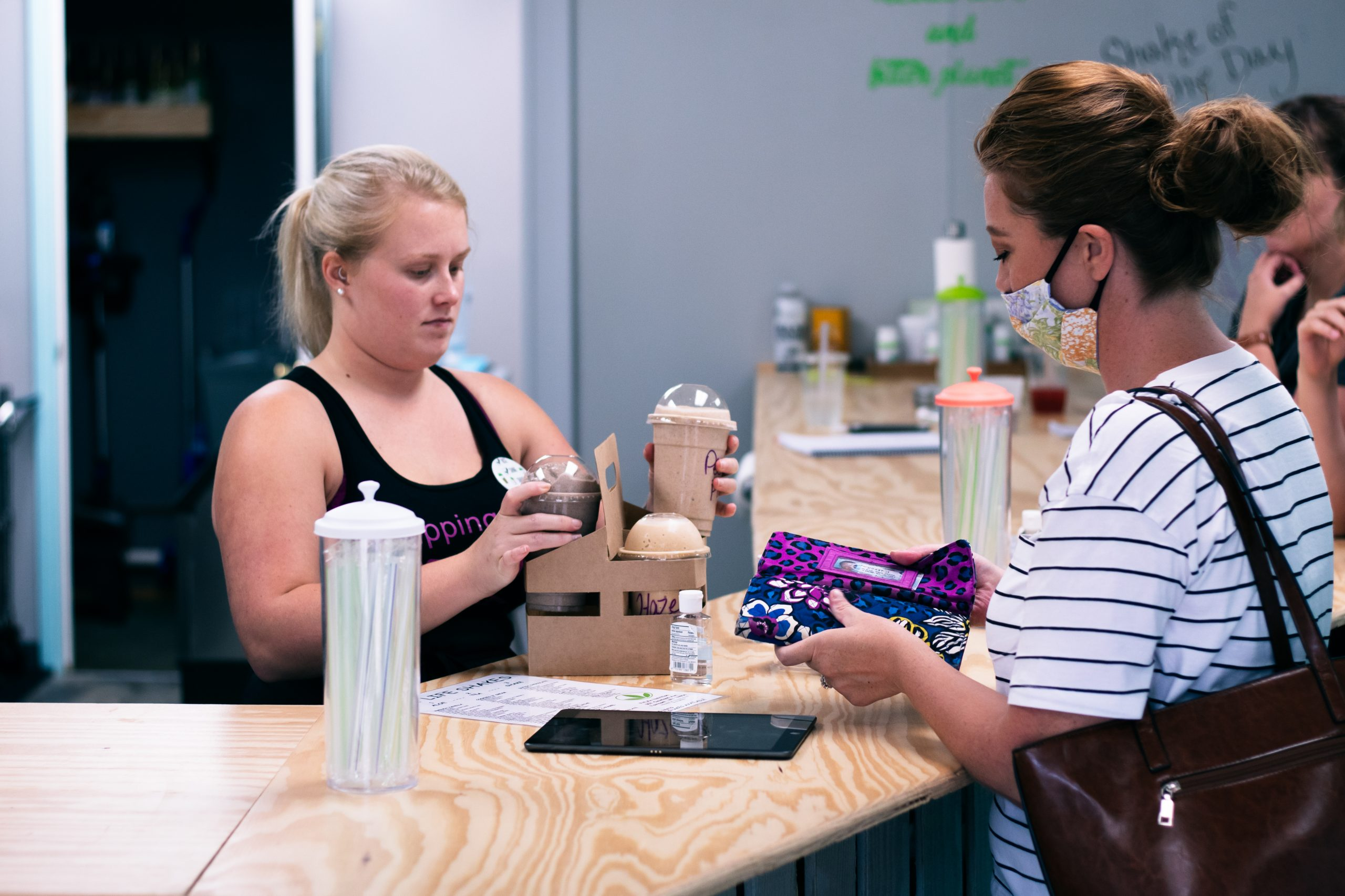 woman handing a patron a drink over a counter
