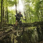 man riding a mountain bike over a large rock in the middle of the woods