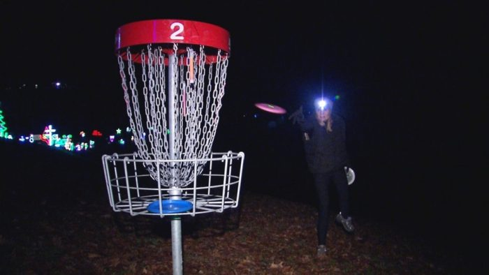 a woman wearing a head light throwing a frisbee into a metal bucket on a pole