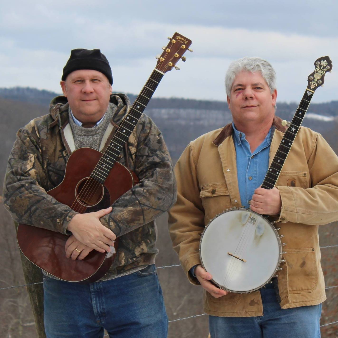 two men standing outside one is holding a banjo and the other a guitar