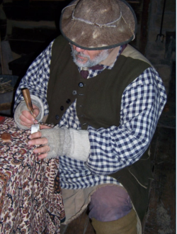 man dressed in frontier clothing working on a powerhorn